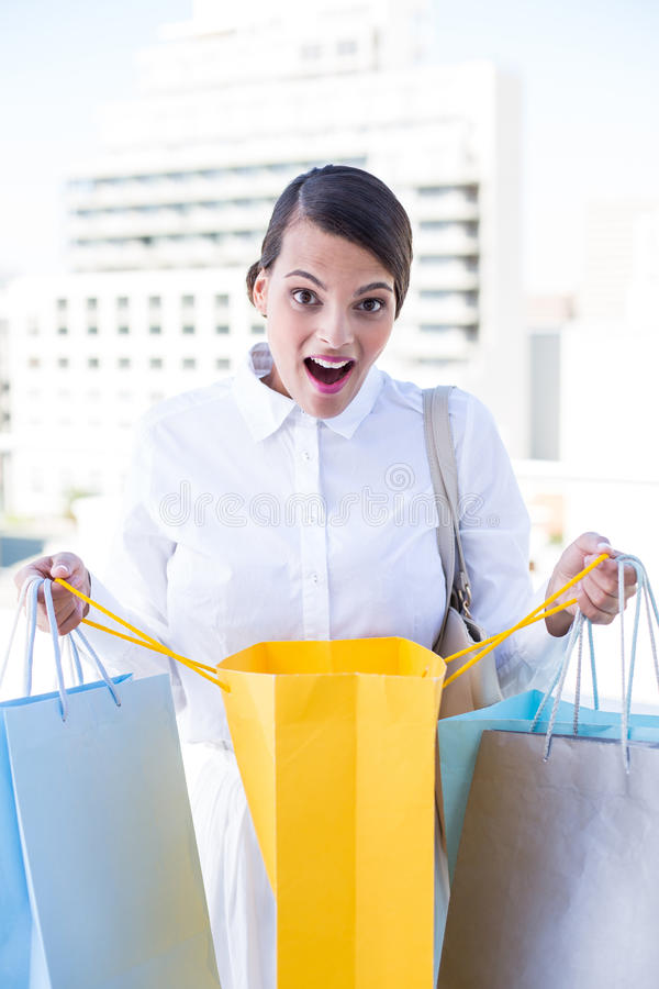 Surprised woman looking in shopping bag stock image