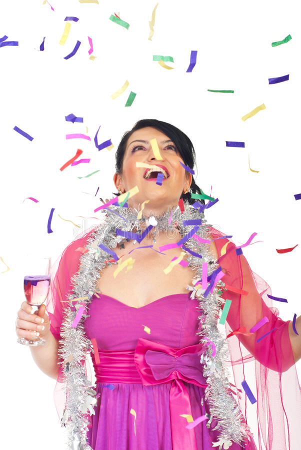 Surprised woman looking up at falling confetti. Surprised beautiful woman with champagne looking up at falling colorful confetti stock photos