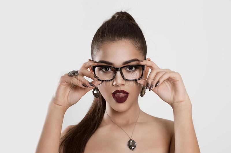 Surprised woman looking at you holding her glasses, not believing her eyes royalty free stock photo