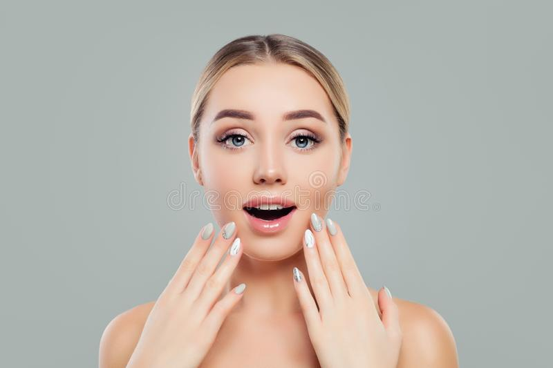Surprised woman with opened mouth. Happy girl with healthy clear skin and manicured hands. Facial treatment stock images