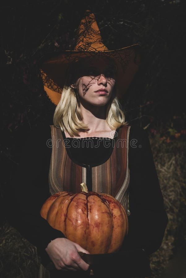 Surprised woman posing with knife and carved pumpkin. Halloween party art design. Happy Halloween. Witch. Happy stock image