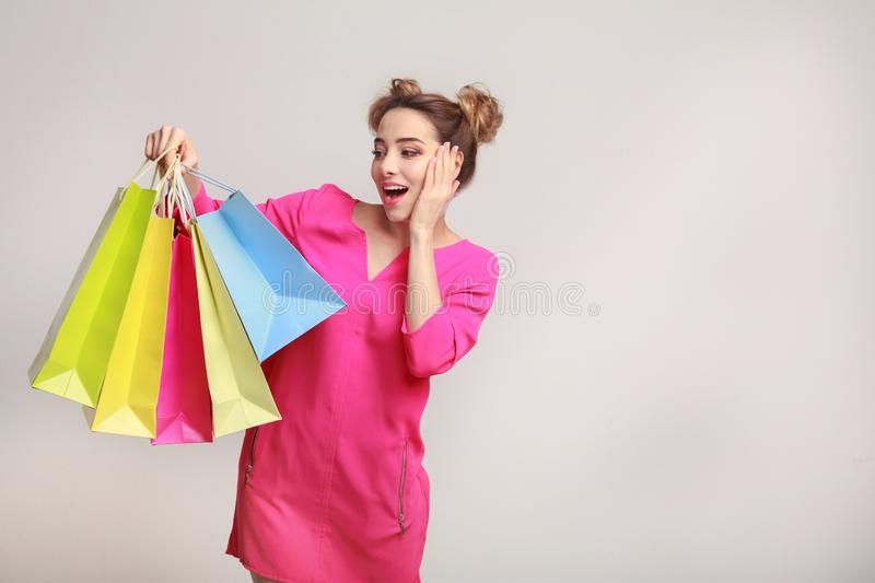 Surprised woman posing with shopping bags and looking at camera stock photos