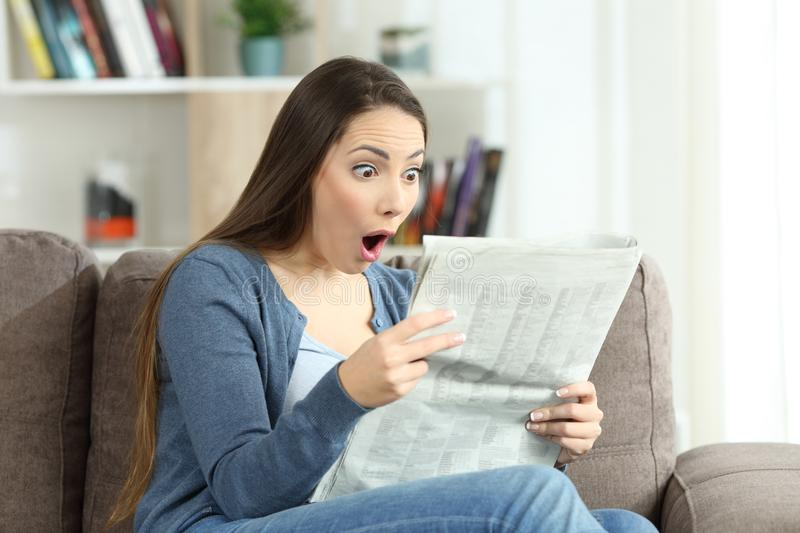 Surprised woman reading a newspaper on a couch royalty free stock image
