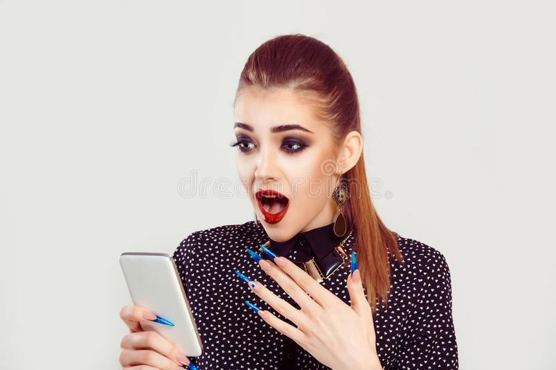 Surprised woman receiving good news by phone. Good news. A surprised happy and shocked woman holds a mobile phone in the right hand looks at it, on a white light royalty free stock photography