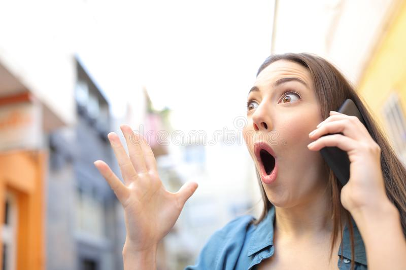 Surprised woman receiving good news talking on phone. In the street royalty free stock photo