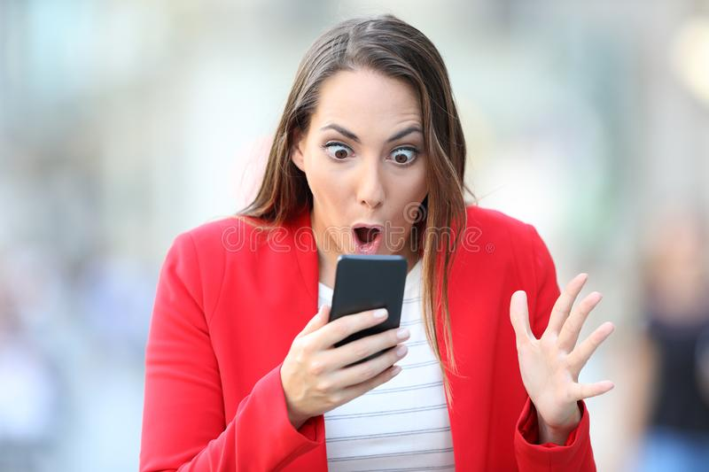 Surprised woman in red checking phone content in the street stock photography