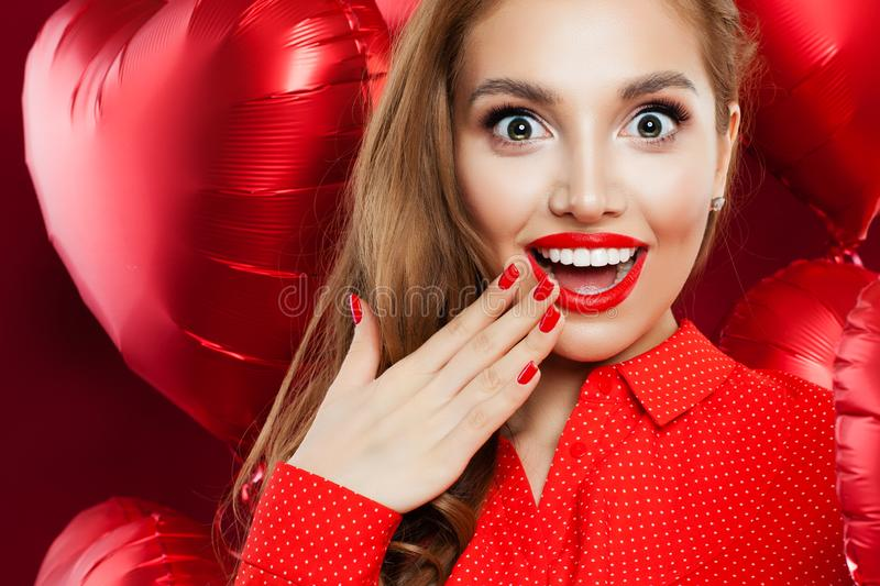 Surprised woman with red lips makeup and manicured hand on red heart balloons background. Excited girl closeup face. Surprise, royalty free stock images