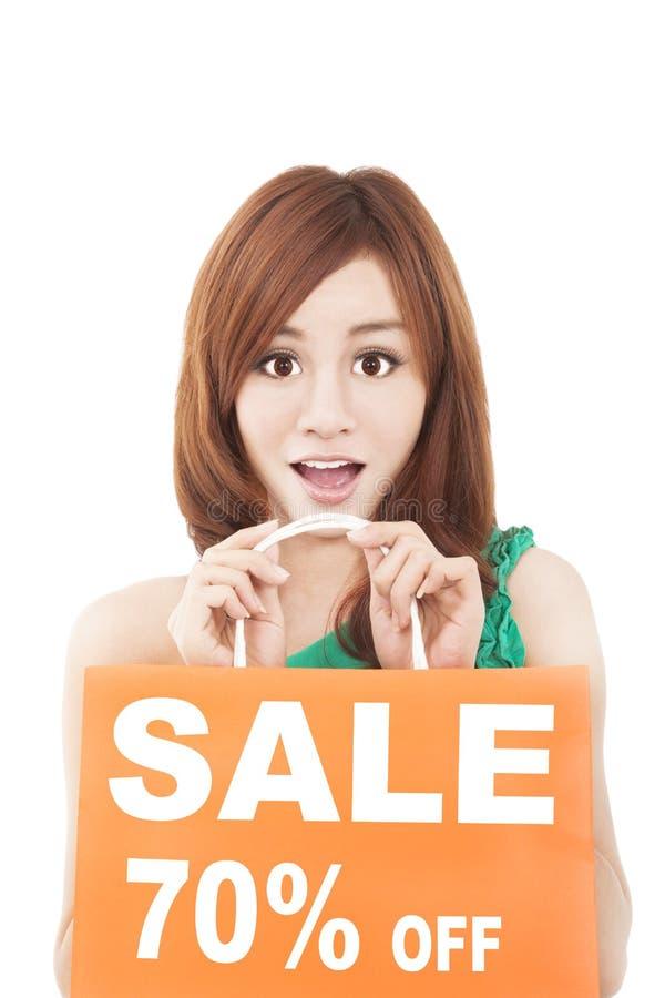 Surprised woman showing shopping bag stock photos