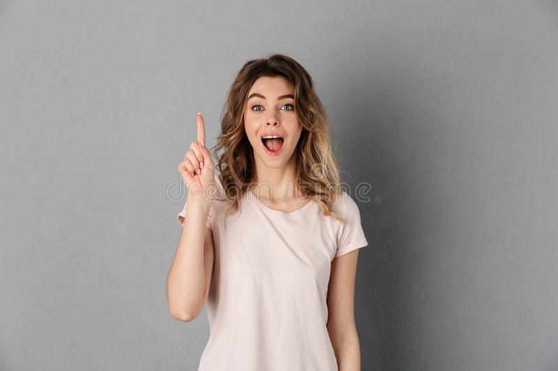 Surprised woman in t-shirt having idea and looking at camera. Surprised woman in t-shirt having idea and looking at the camera with open mouth over grey royalty free stock photo