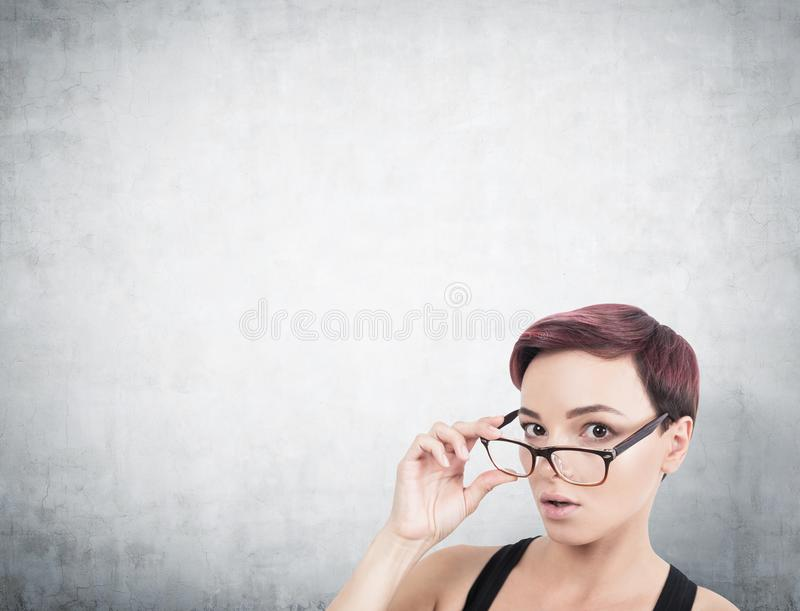 Surprised woman taking off glasses, concrete stock image