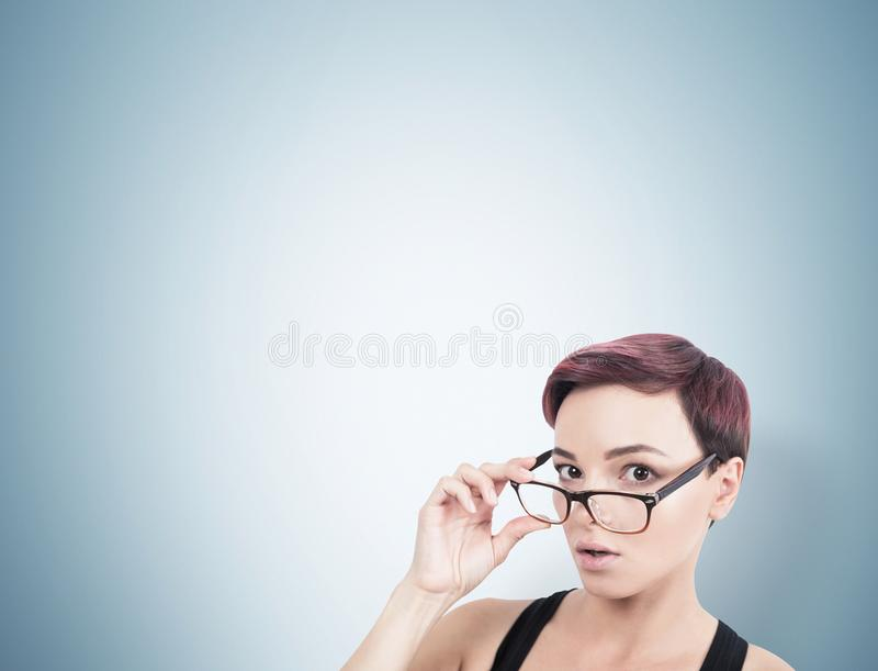 Surprised woman taking off glasses, gray royalty free stock photos