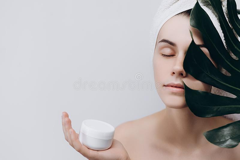 A surprised woman with a towel on her head holds a large green leaf and Cream for Face. stock images