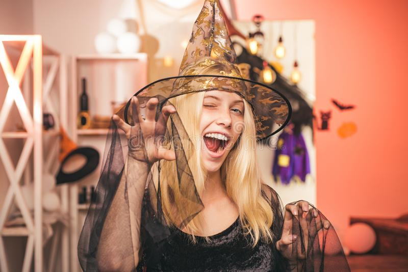 Surprised woman in witches hat and costume on red Halloween background. Beautiful young surprised woman in witches hat stock images