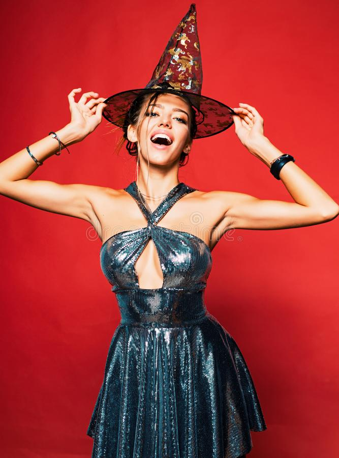 Surprised woman in witches hat and costume on red Halloween background. Witch vampire concept. Glamour Fashion Sexy stock image