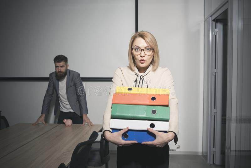 Surprised woman and bearded man on background. Business woman in glasses hold file folders. secretary with office. Surprised women and bearded men on background stock images