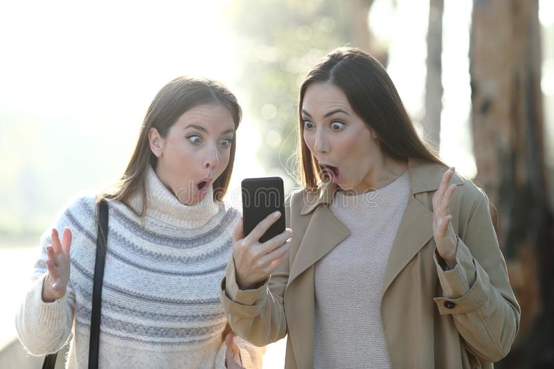 Surprised women checking phone in a foggy park royalty free stock photography