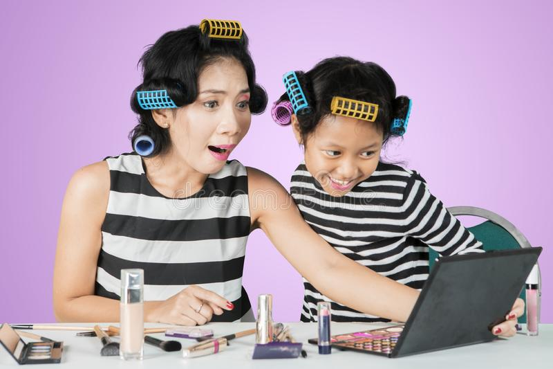 Surprised woman after doing makeup with child stock photo