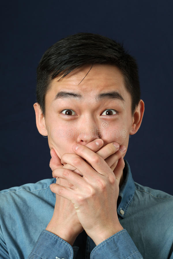 Surprised young Asian man covering mouth with palms stock photos