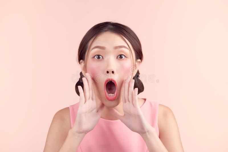 Surprised young asian woman shouting over pink background.  stock images