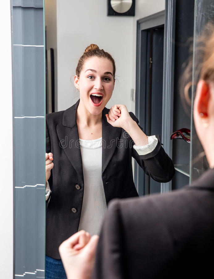 Surprised young beautiful business woman laughing in front of mirror. Surprised young beautiful business woman enjoying getting excited with dynamic hand gesture stock photo