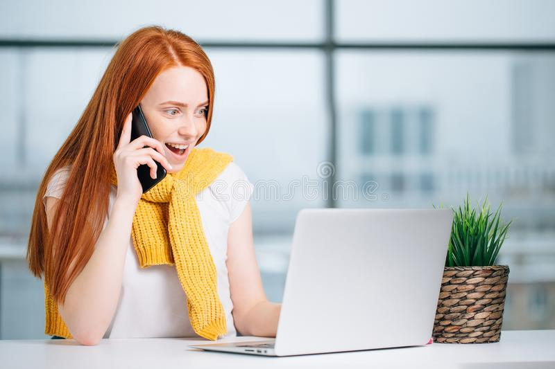 Surprised young brunette woman alone with laptop and mobile phone in summer cafe royalty free stock images