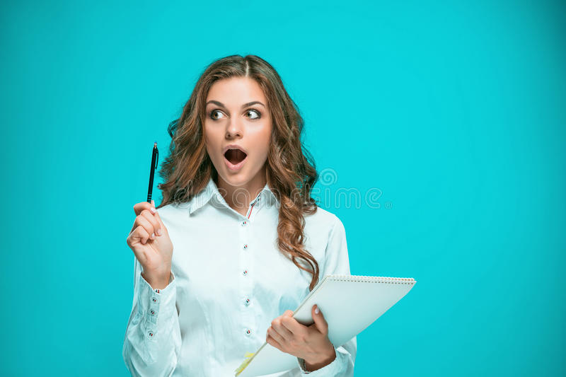 Surprised young business woman with tablet for notes on blue background stock photos