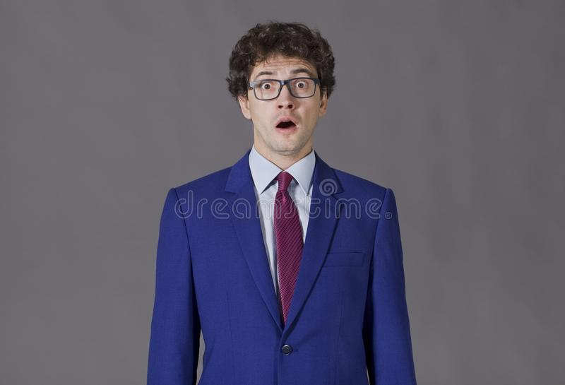Surprised young businessman on grey background stock photo