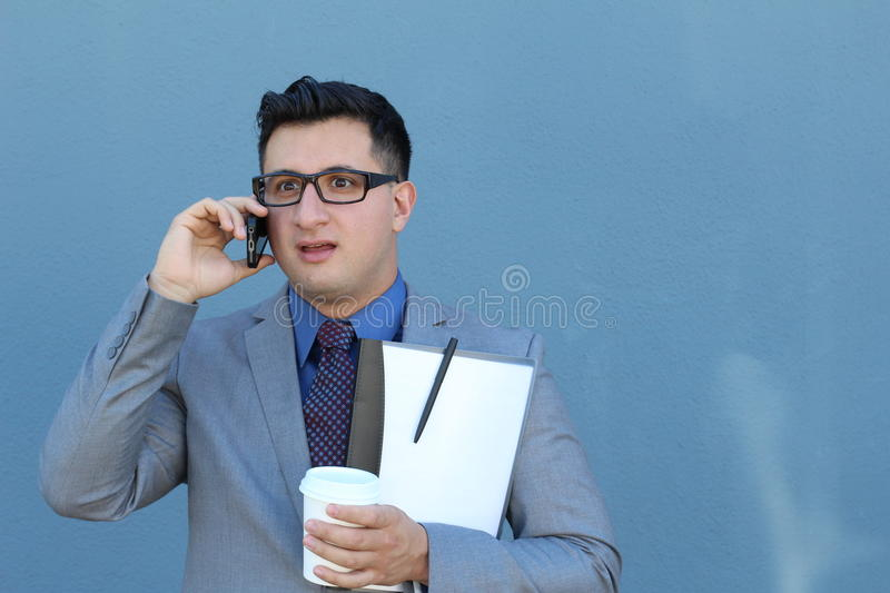 Surprised young businessman talking on phone over blue background - Stock image.  royalty free stock photography