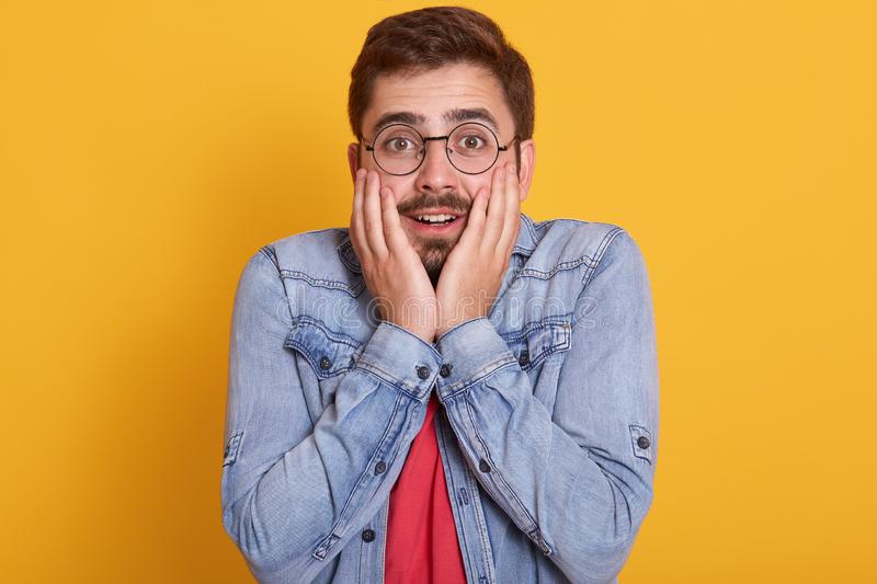 Surprised young Caucasian man with eyewear and astonished facial expression, dressed red tshirt and denim jacket, stands against. Yellow background, keeps hands stock images