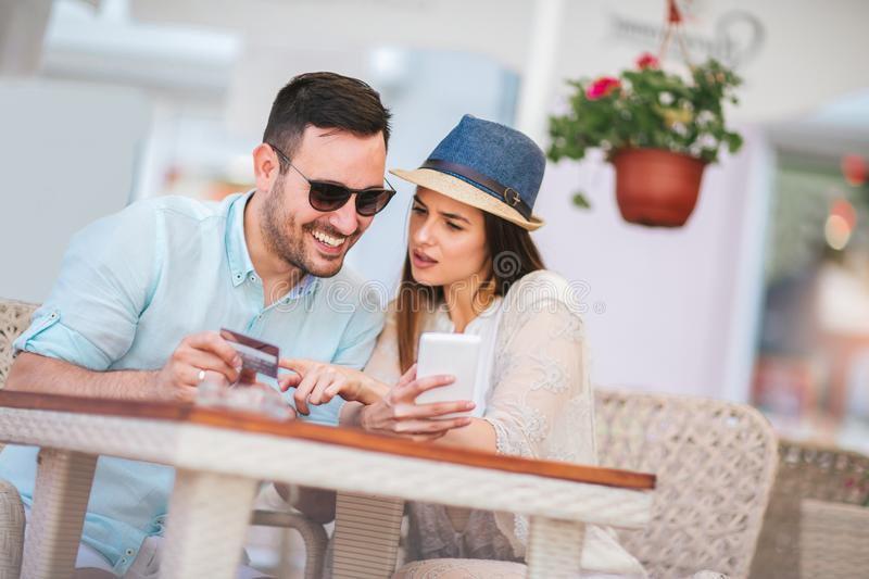 Surprised young couple doing online shopping through smart phone. And credit card at cafe stock photos
