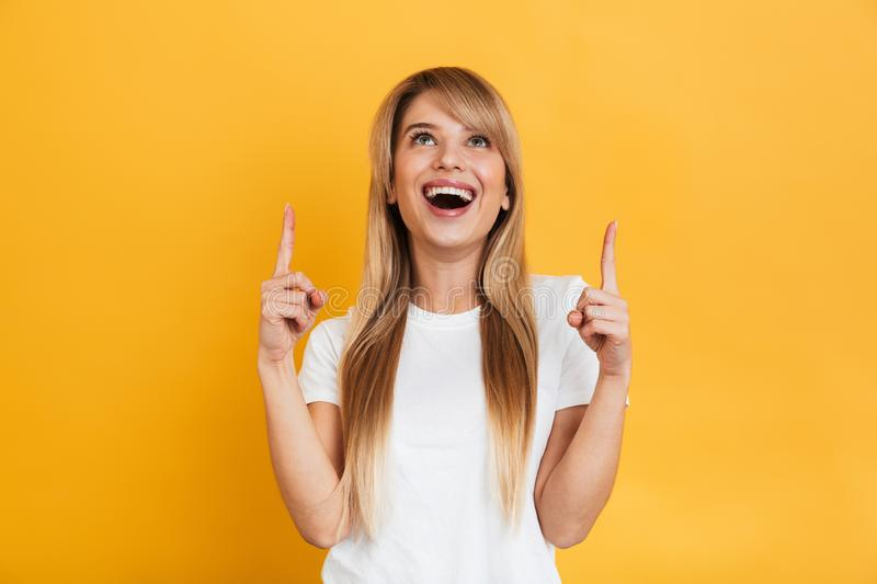 Surprised young excited shocked blonde woman posing isolated over yellow wall background pointing. Image of a surprised dreaming happy young excited shocked stock images