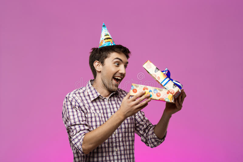 Surprised young handsome man opening birthday gift over purple background. Surprised young handsome man smiling, opening birthday gift over purple background royalty free stock photos