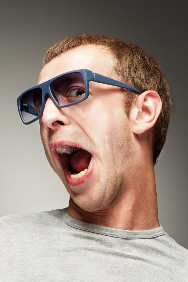 Surprised young man. Young man in sun glasses with surprised smile stock photography