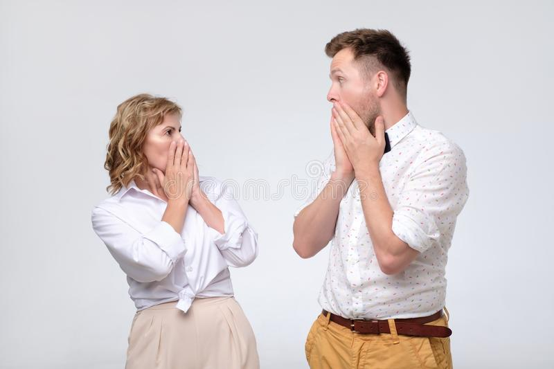 Surprised young man and mature woman looking at each other in full disbelief. Surprised young men and mature women looking at each other in full disbelief royalty free stock photos