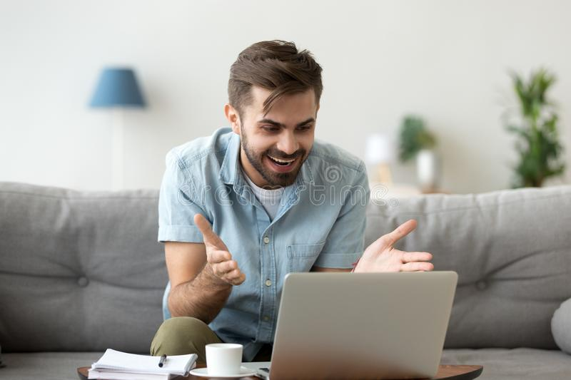 Surprised young man read news on laptop. Millennial young man sitting on couch in living room at home alone using looking at computer screen feels happy and stock images