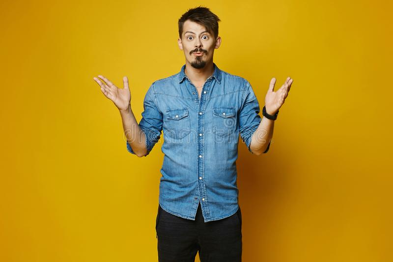 Surprised young man, stylish hipster with beard and mustache in fashionable jeans shirt at yellow background, isolated royalty free stock photos