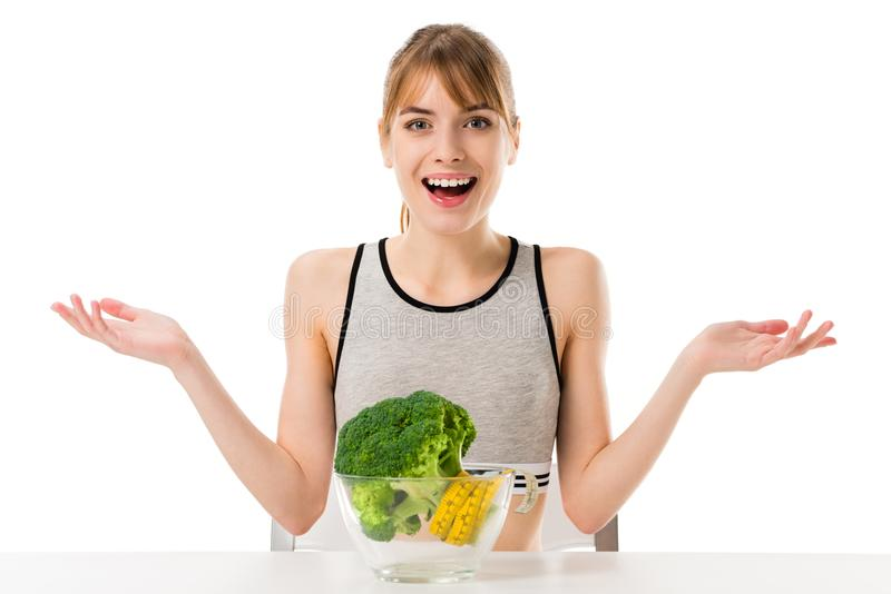 surprised young slim woman with broccoli covered in measuring tape in bowl royalty free stock images