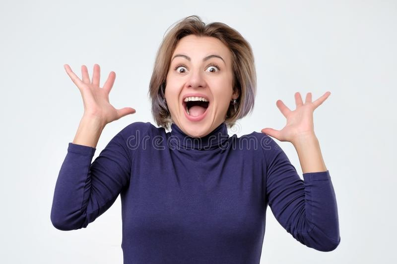 Surprised young woman in blue clothes shouting shocked with great news. stock photo