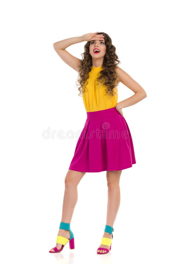 Surprised Young Woman In Colorful High Heels And Pink Mini Skirt Is Looking Up. Surprised young woman in colorful high heels, pink mini skirt and yellow top is stock photography