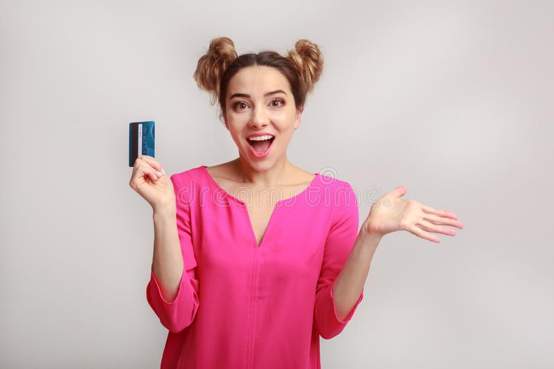 Surprised young woman with credit card over background stock photography