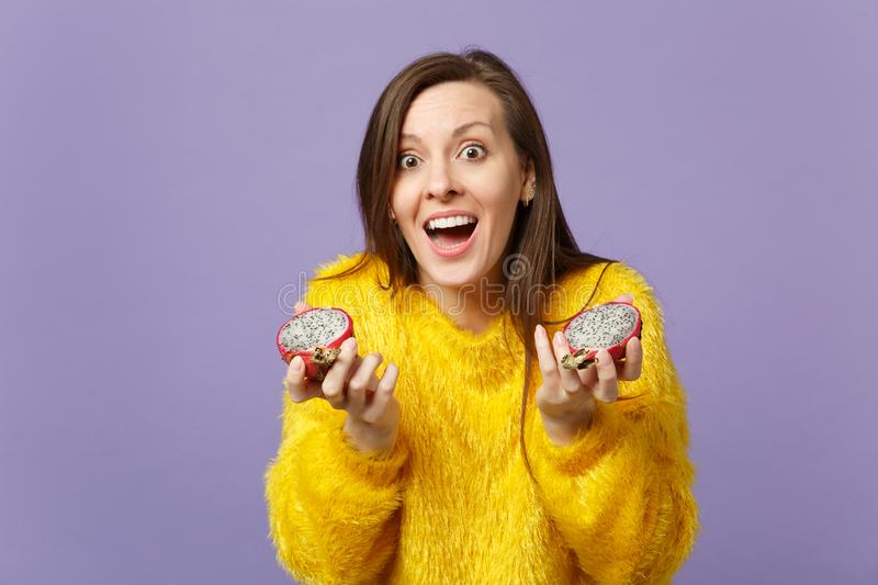 Surprised young woman in fur sweater keeping mouth open holding halfs of pitahaya, dragon fruit isolated on violet royalty free stock photos