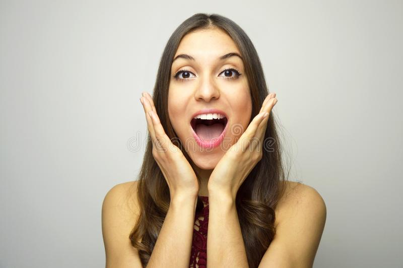 Surprised young woman with hands near open mouth looking at camera on gray background royalty free stock photos
