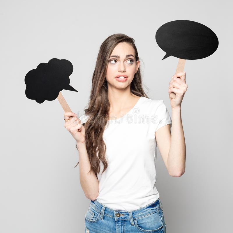 Surprised young woman holding speech bubbles royalty free stock photos