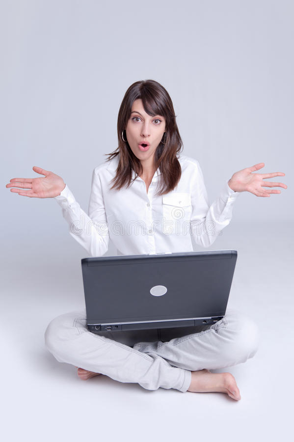 Surprised Young Woman With Laptop On The Floor Stock Photo