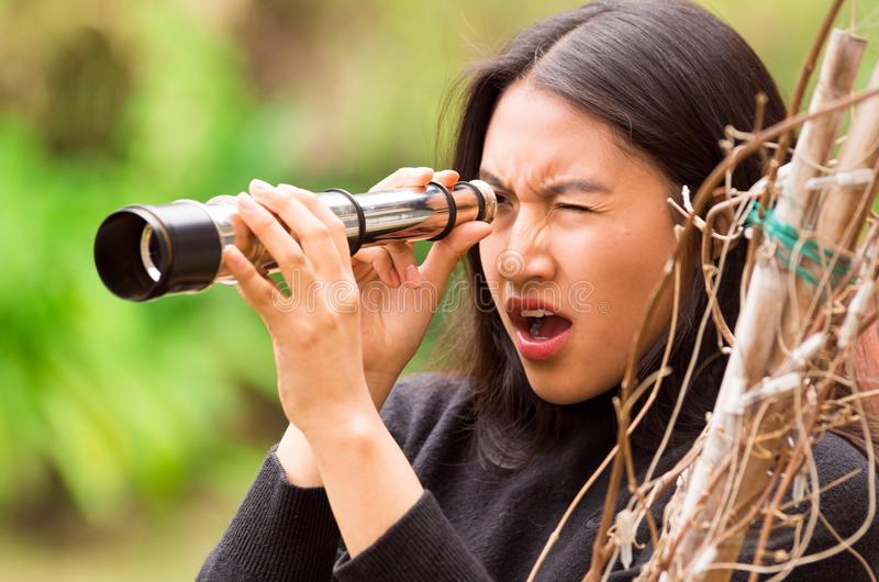 Surprised young woman looking through black monocular in the forest in a blurred background royalty free stock photos
