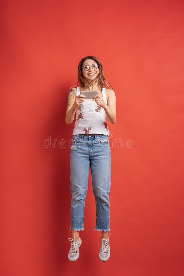 Surprised young woman always on mobile on red background royalty free stock image