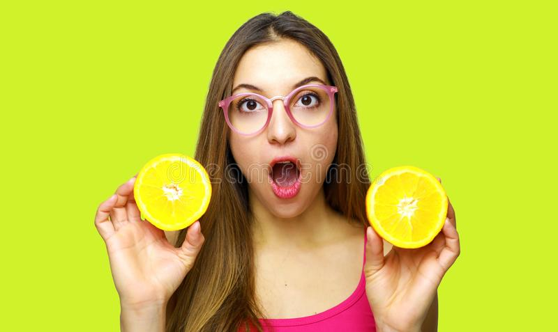 Surprised young woman in summer clothes holding halfs of fresh orange fruit isolated on yellow background. People vivid lifestyle stock photography