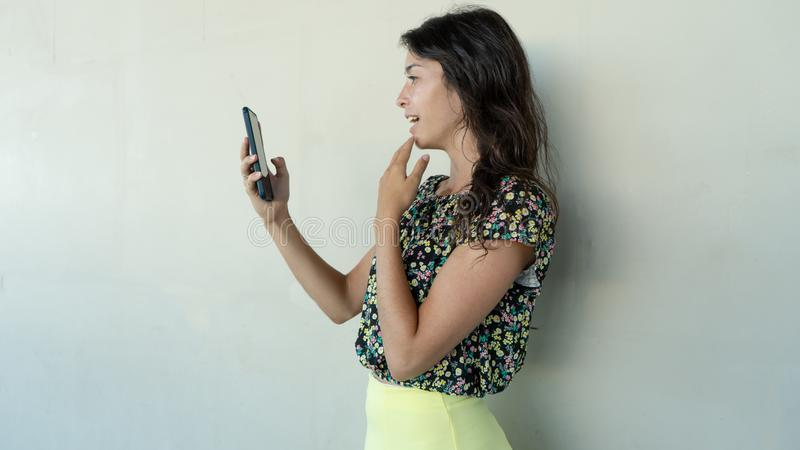 Surprised Young Woman Using Mobile Phone reading news and hand in her open mouth. Teenager look screen Holding cellphone with stock images