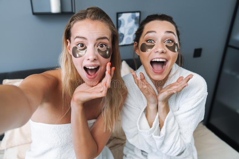 Surprised young women take selfie by camera stock photos