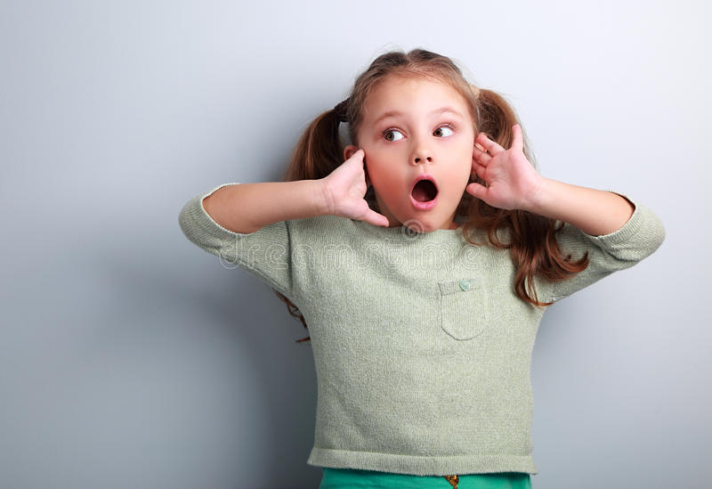 Surprising kid girl with long hair with opened mouth and hand ne royalty free stock images